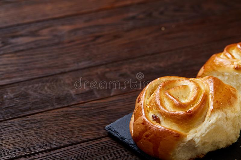 Homemade rose buns on stony cutting board over rustic vintage background, close-up, shallow depth of field royalty free stock photography