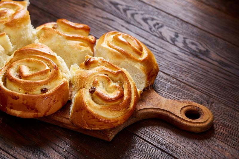 Homemade rose buns on wooden cutting board over rustic vintage background, close-up, shallow depth of field royalty free stock photo