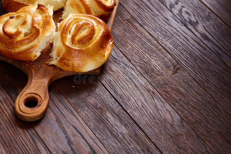 Homemade rose buns on wooden cutting board over rustic vintage background, close-up, shallow depth of field stock image