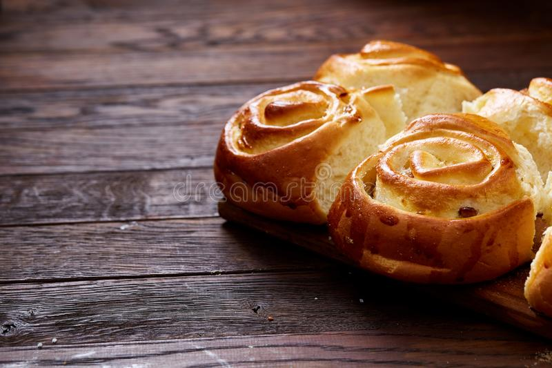 Homemade rose buns on wooden cutting board over rustic vintage background, close-up, shallow depth of field royalty free stock image