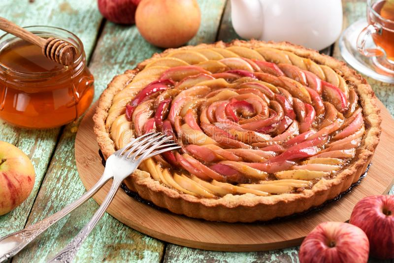 Homemade rose shape apple pie with red apples, honey and tea on. Shabby blue background closeup stock images