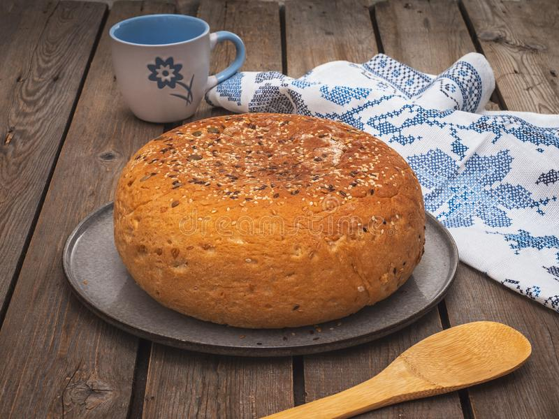 Homemade round bread with flax and sesame seeds on a round plate on an old plank table, frying and a cotton towel with a pattern. Homemade round bread with flax stock photos