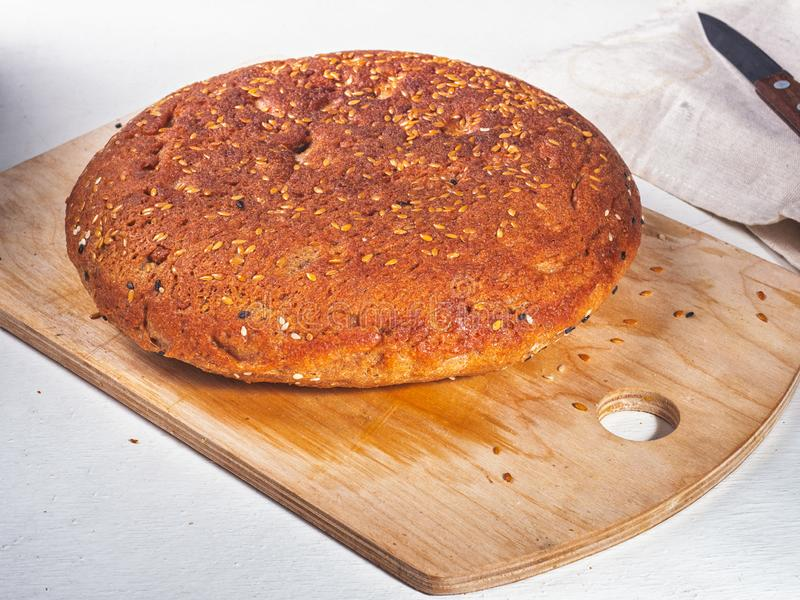 Homemade round bread made of coarse flour sprinkled with white and black seeds of sesame seeds lies on a kitchen wooden board and royalty free stock photo