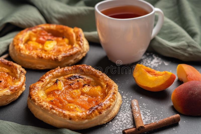 Homemade round puffs with peaches on a dark background with a linen napkin. Next to white cup with black tea, peach slices, royalty free stock image