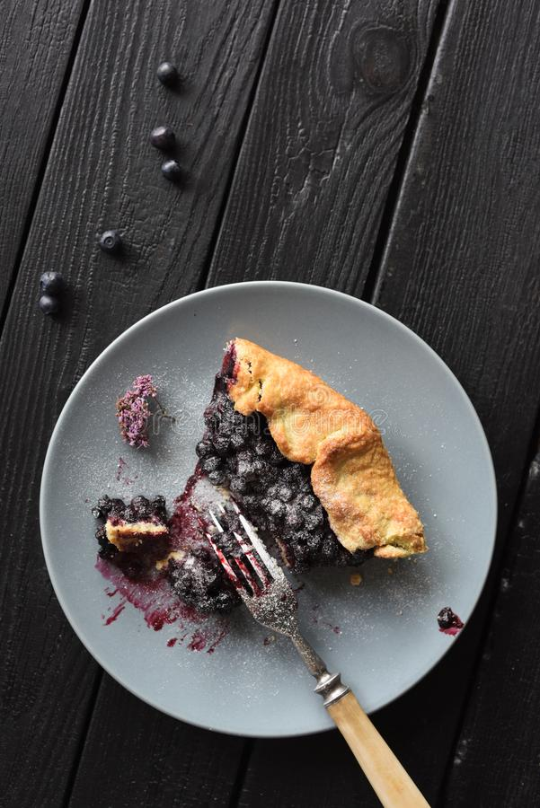 Homemade rustic pie. Delicious crusty blueberry galette in gray plate on black background copy space royalty free stock photo