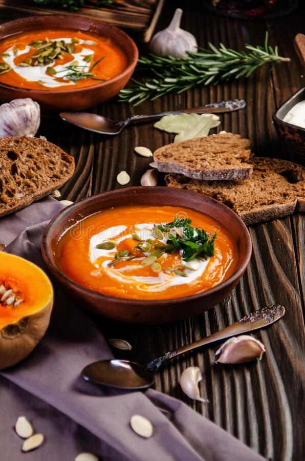 Homemade rustic pumpkin soup with seeds in clay dish on wooden table with bread spices and greens aside.  stock photos