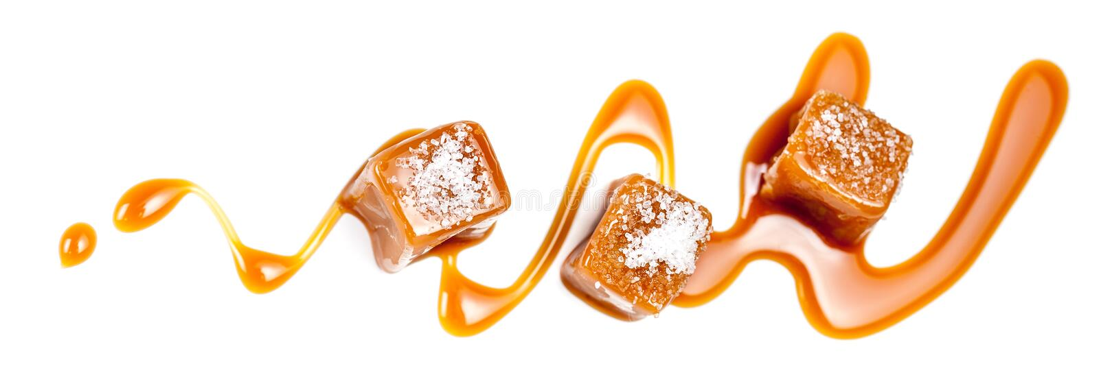 Homemade salted caramel pieces isolated on white background. Golden Butterscotch toffee candy caramels macro. Homemade salted caramel pieces isolated on white royalty free stock image