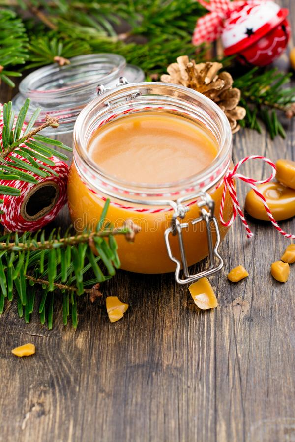 Homemade salted caramel sauce in a glass jar and Christmas decor on wooden background stock photography