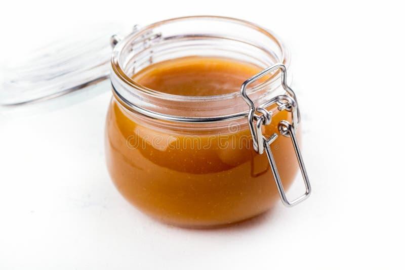 Homemade salted caramel sauce in a glass jar stock photos