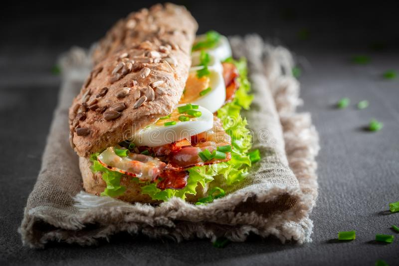 Homemade sandwich with bacon, chive and eggs. On grey table stock images