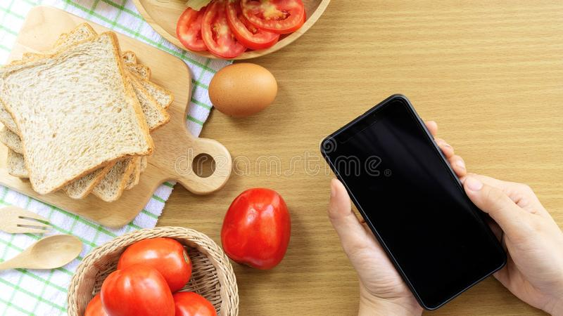 Homemade sandwich breakfast preparing. Whole wheat bread is stacked on a wooden cutting board placed on a white fabric, green chec stock images