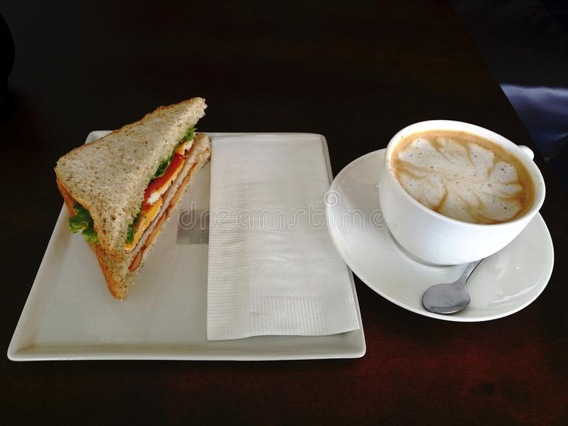 Homemade sandwich with cheese and ham and Latte coffee cup in n a in white plate on green wooden table stock images