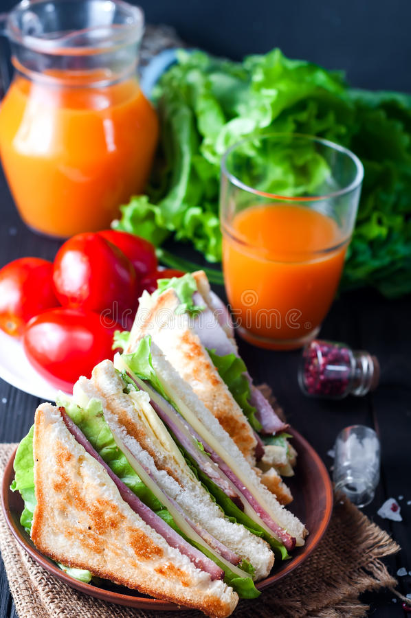 Homemade sandwich with salad and juice as a healthy breakfast royalty free stock images