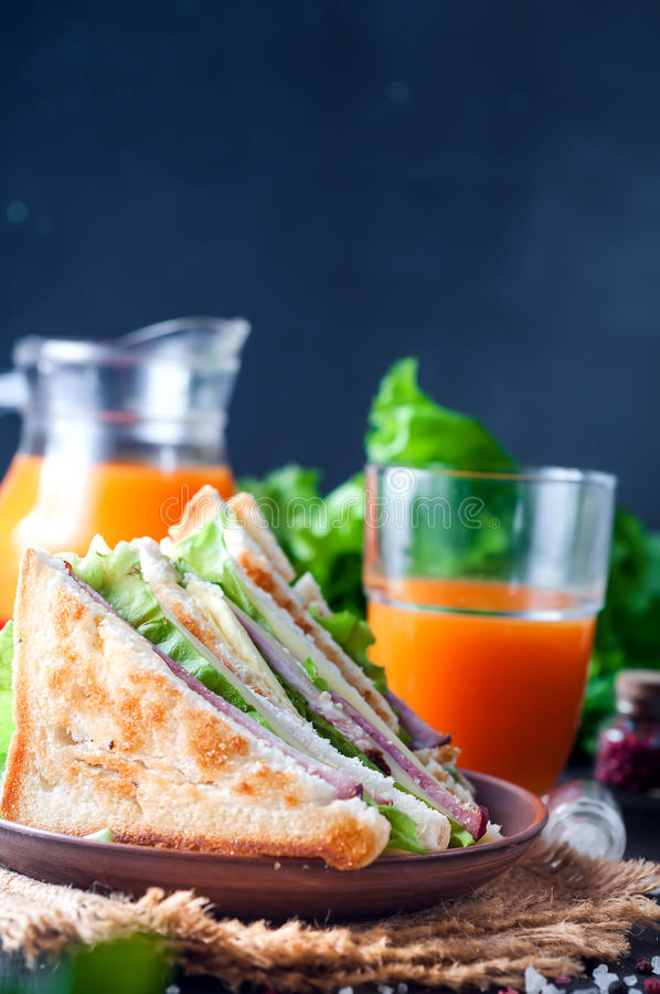 Homemade sandwich with salad and juice as a healthy breakfast royalty free stock image