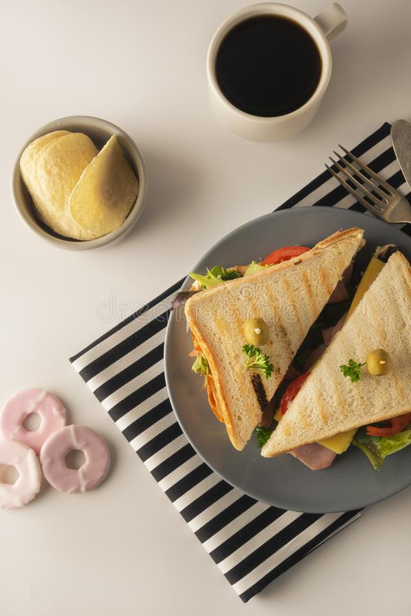 Homemade sandwich. Toasted double panini with ham, cheese fresh vegetables. Snack at work or lunch. Light background. Healthy food lettuce turkey olive bread royalty free stock images
