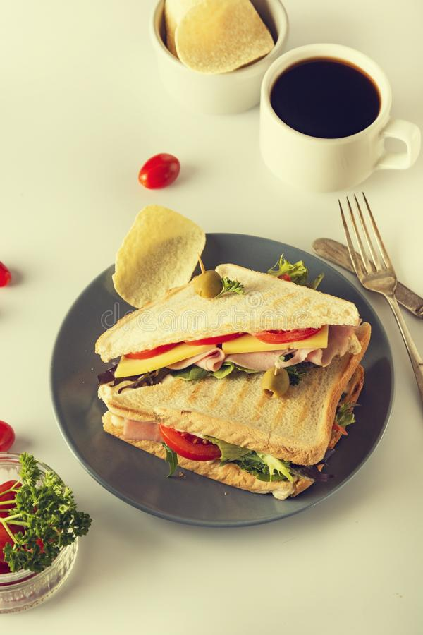 Homemade sandwich. Toasted double panini with ham, cheese fresh vegetables. Snack at work or lunch. Light background. Healthy food lettuce turkey olive bread stock photos