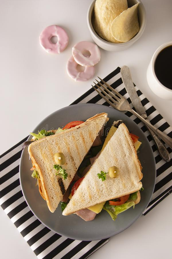 Homemade sandwich. Toasted double panini with ham, cheese fresh vegetables. Snack at work or lunch. Light background stock photos