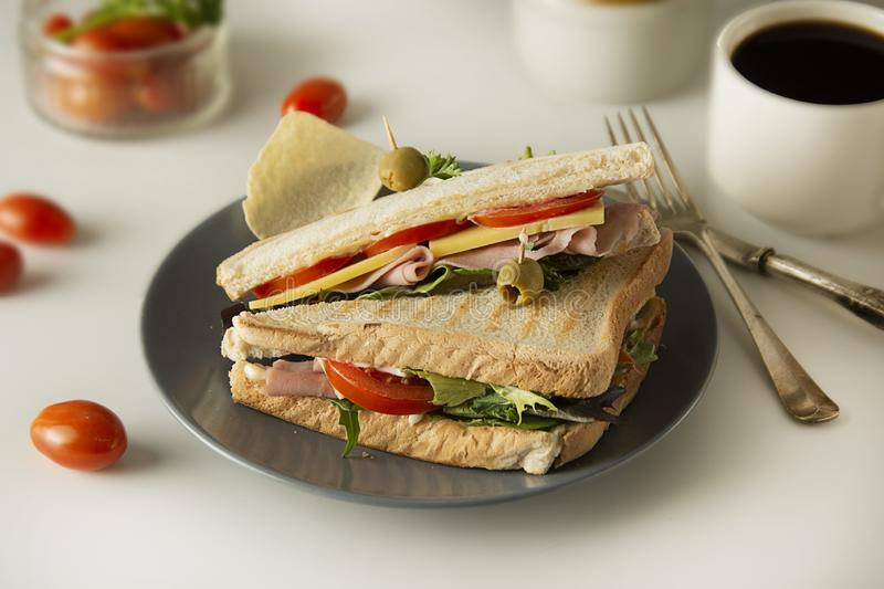 Homemade sandwich. Toasted double panini with ham, cheese fresh vegetables. Snack at work or lunch. Light background royalty free stock photos