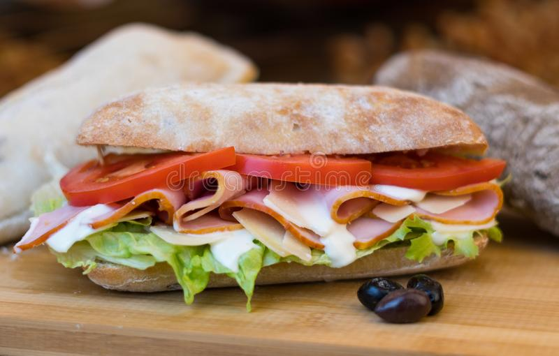 Homemade Sandwich with ham, fresh tomatoes, green salad and sauce royalty free stock photo