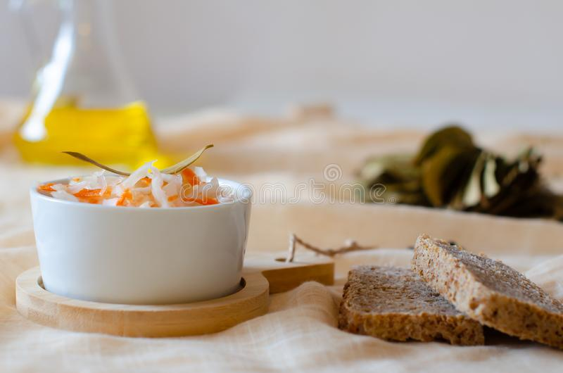 Homemade sauerkraut with carrots, sunflower oil, bread and black pepper in a bowl on a linen napkin. stock photos
