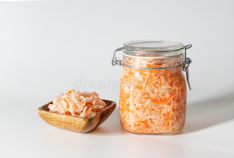 Homemade sauerkraut. Fermented food. Sauerkraut with carrots in a glass jar and a wooden bowl on a white background royalty free stock images
