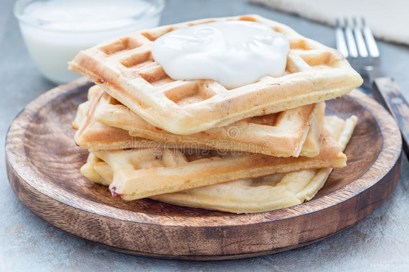 Homemade savory belgian waffles with bacon and shredded cheese, served with plain yogurt, on wooden plate, horizontal. Homemade savory belgian waffles with bacon royalty free stock image