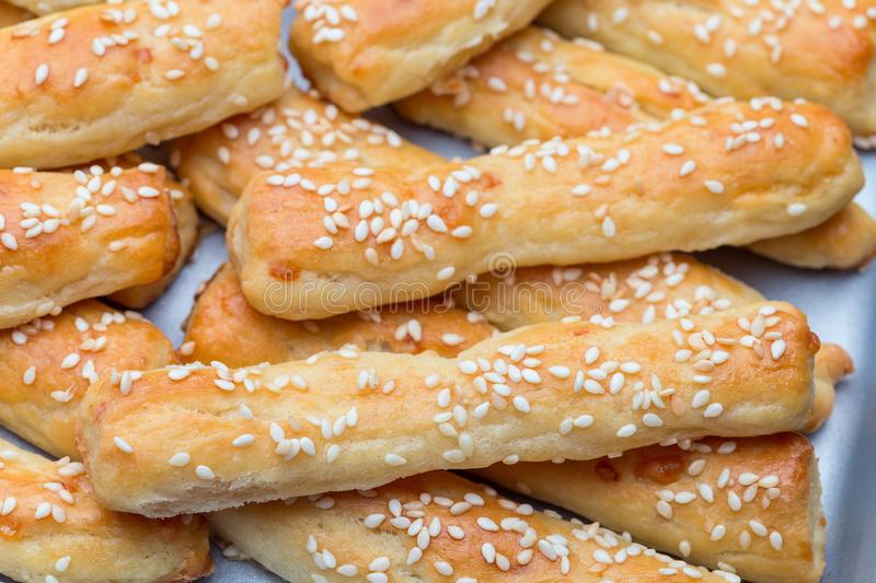 Homemade savory bread sticks with cheese and sesame on a baking tray, horizontal, closeup royalty free stock photography