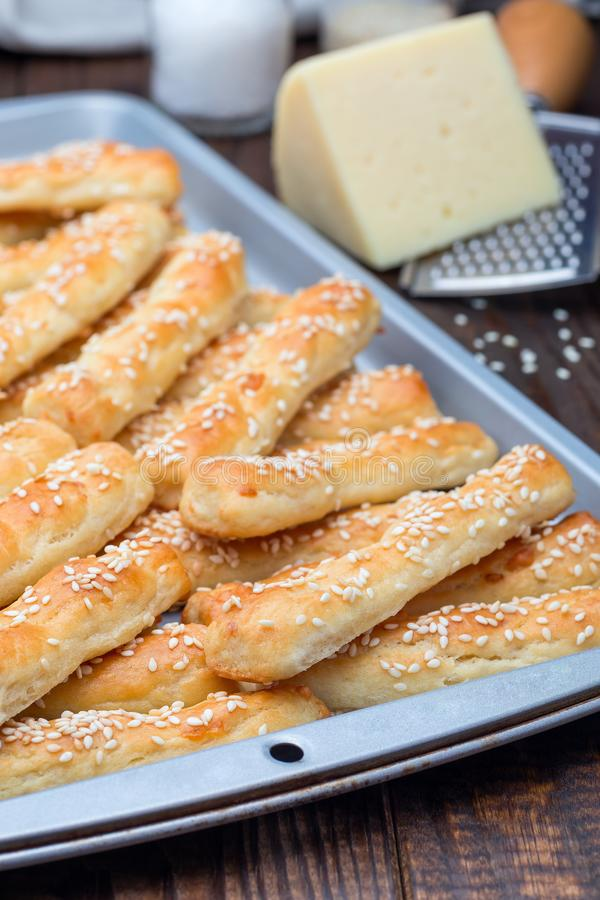 Homemade savory bread sticks with cheese and sesame on baking tray, vertical royalty free stock photo