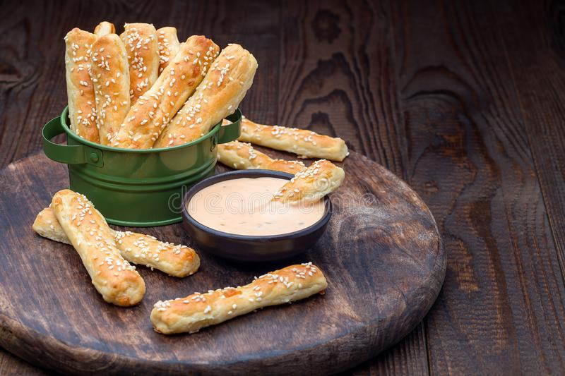 Homemade savory bread sticks with cheese and sesame in a basket, served with sauce on wooden board, horizontal, copy space stock photo