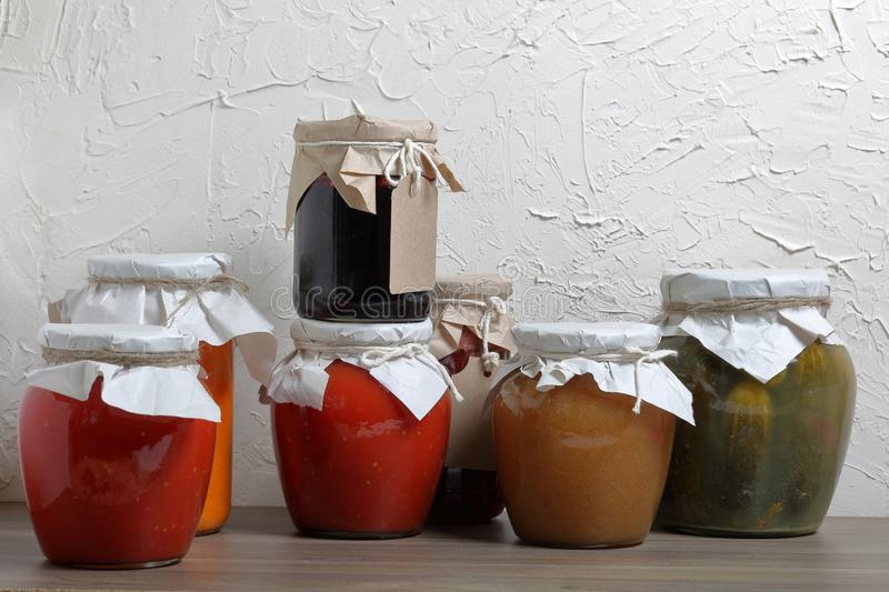 Homemade seasonal preparations. In banks, canned vegetables, fruits. The neck of the cans is wrapped in paper and tied with rope.  stock photo
