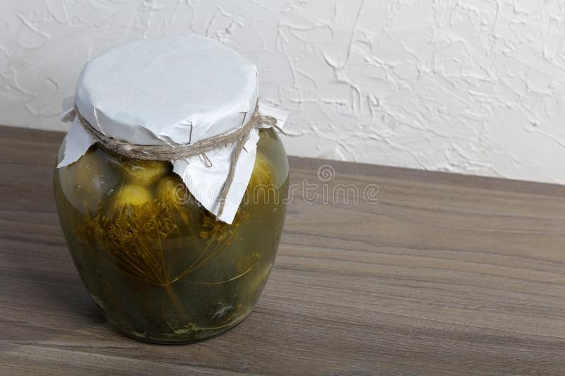 Homemade seasonal preparations. Pickled cucumbers in a glass jar. The neck of the can is wrapped in paper and tied with a rope.  royalty free stock images