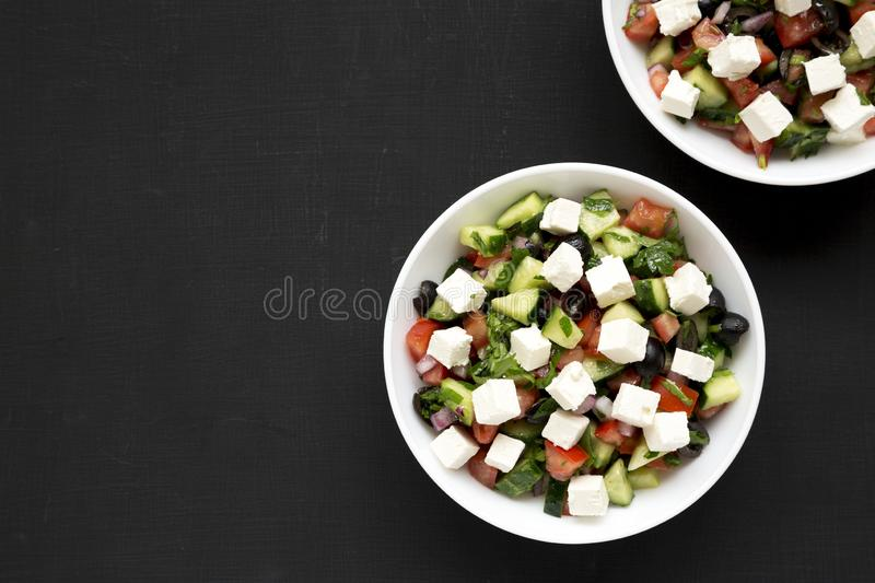 Homemade Shepherd`s salad with cucumbers, feta and parsley in white bowls on a black background, top view. From above, overhead, royalty free stock images