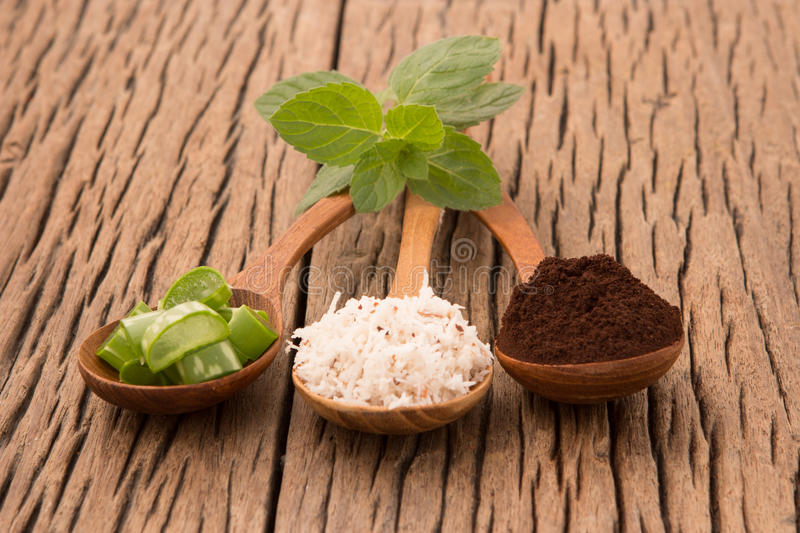 Homemade skin care and body scrub with natural coffee, aloe vera. Coconut up on wooden table royalty free stock photo