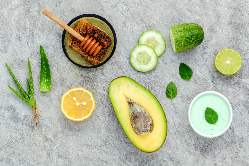 Homemade skin care and body scrub with natural ingredients avocado ,aloe vera ,lemon,cucumber and honey set up on stone. Background royalty free stock images