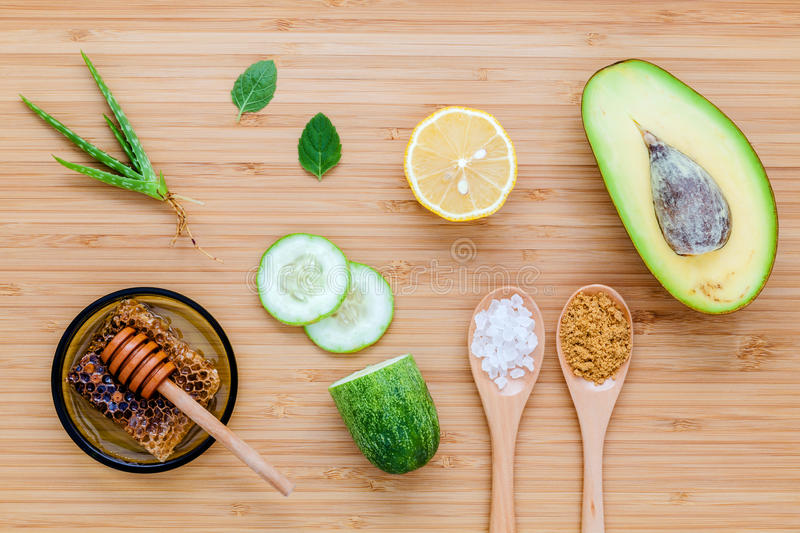 Homemade skin care and body scrub with natural ingredients avocado ,aloe vera ,lemon,cucumber and honey set up on wooden. Background royalty free stock photo