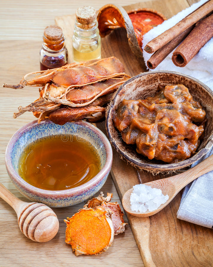 Homemade skin care and body scrub with natural ingredients tamarind, honey, himalayan salt ,turmeric and cinnamon set up on. Wooden background stock photography