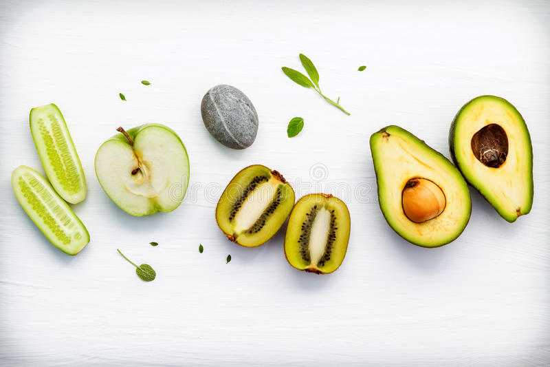 Homemade skin care and body scrubs with green natural ingredient. S cucumber , avocado ,green apple,kiwi, and spa stone setup on white wooden background with stock photos