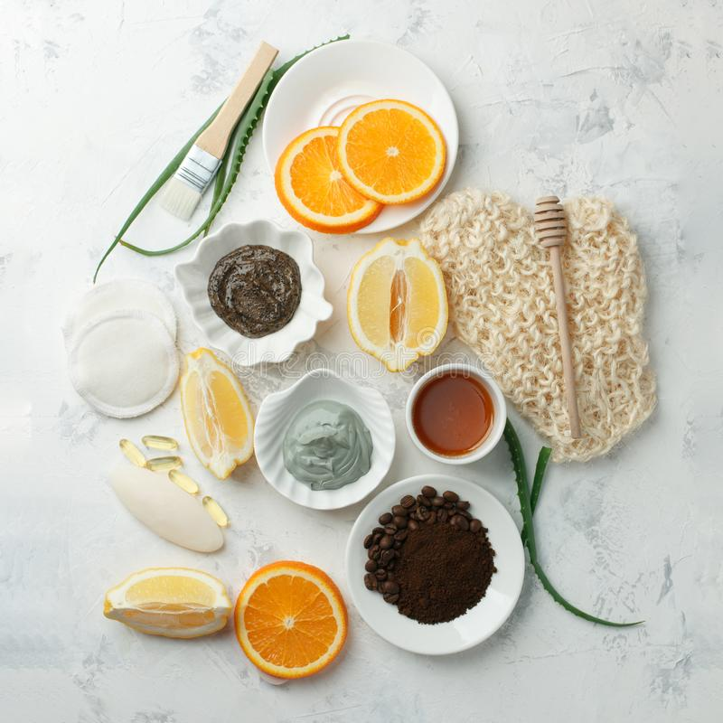 Homemade skin care and body scrubs and mask with natural ingredients aloe vera, lemon, coffee, oranges, clay, honey set up on. White wooden background with flat stock images