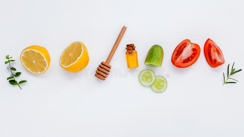 Homemade skin care and body scrubs with natural ingredients lemon,cucumber ,tomato slice,mint ,rosemary and honey set up on white royalty free stock photography