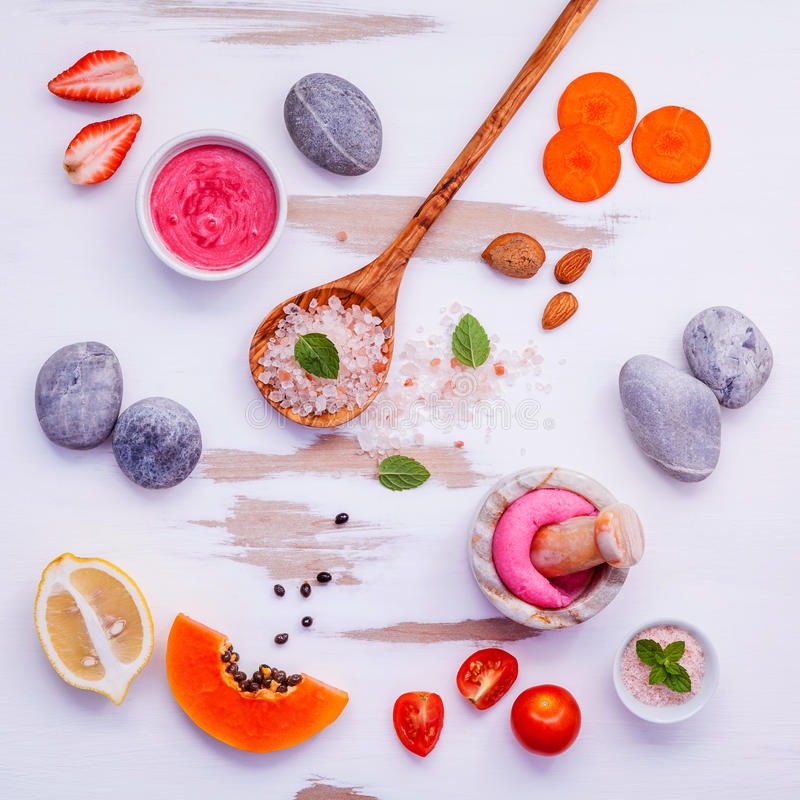 Homemade skin care and body scrubs with red natural ingredients. Strawberry , tomato ,himalayan salt, ripe papaya, carrot and spa stone setup on white wooden stock photo