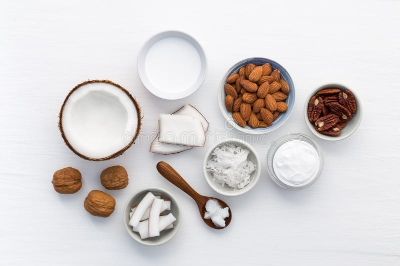 Homemade skin care products on white wooden table background. Co. Conut, oil, walnut, almond, scrub, milk and lotion from top view. Good for space and background stock images