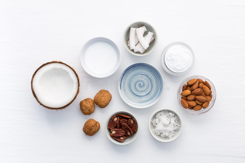 Homemade skin care products on white wooden table background. Co. Conut, oil, walnut, almond, scrub, milk and lotion from top view. Good for space and background royalty free stock photo