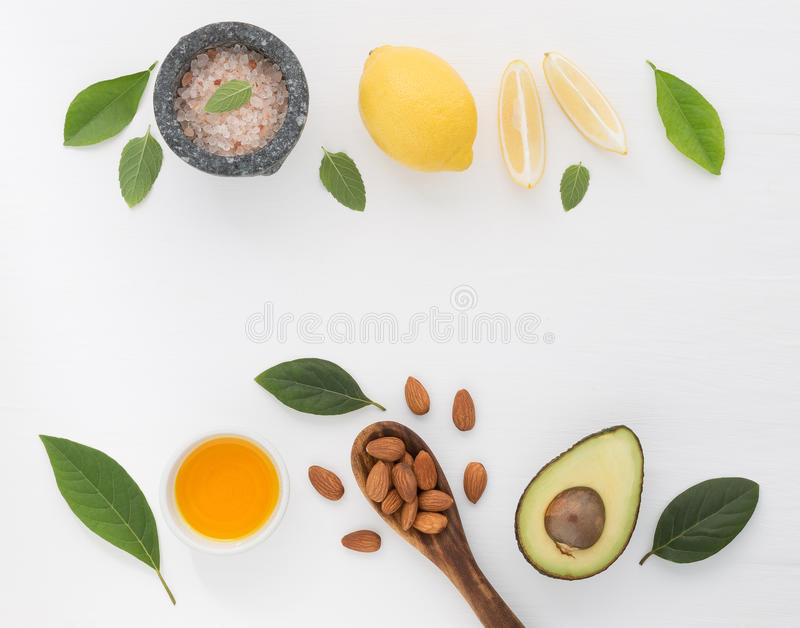 Homemade skincare and body scrubs with natural ingredients almond, avocado, lemon, sea salt, peppermint leaves and oil set up on royalty free stock image