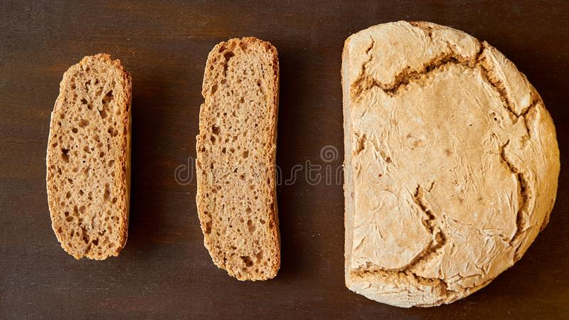 Homemade sliced fresh bread on the wooden background ready to eat. Just baked round bread on the brown table with free copy space stock photography
