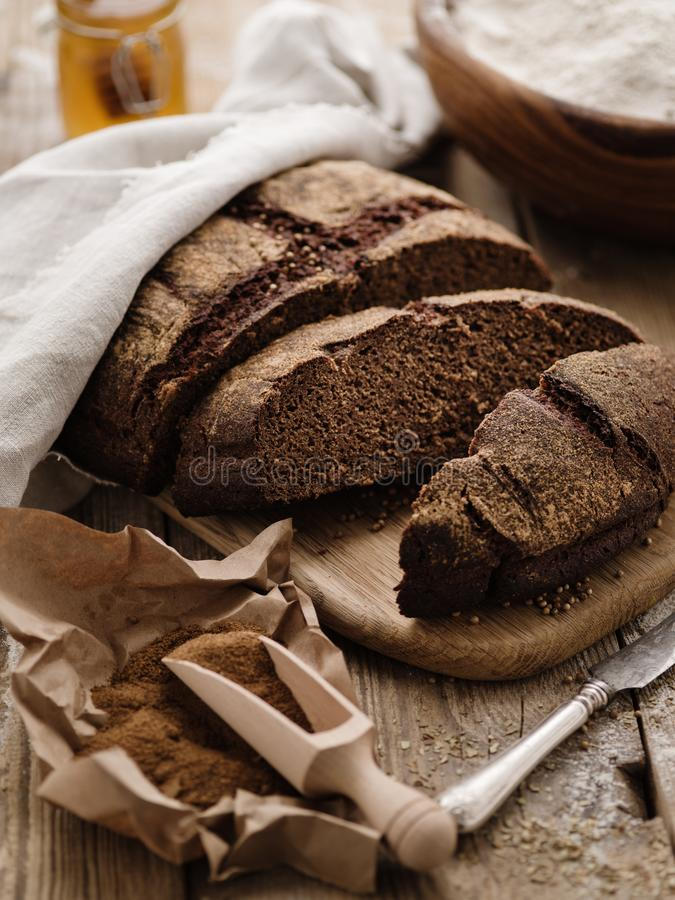 Homemade sliced round rye bread on a wooden table with malt and royalty free stock images