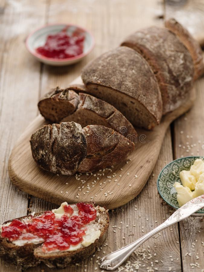 Homemade sliced rye bread on a wooden table and a sandwich with stock images