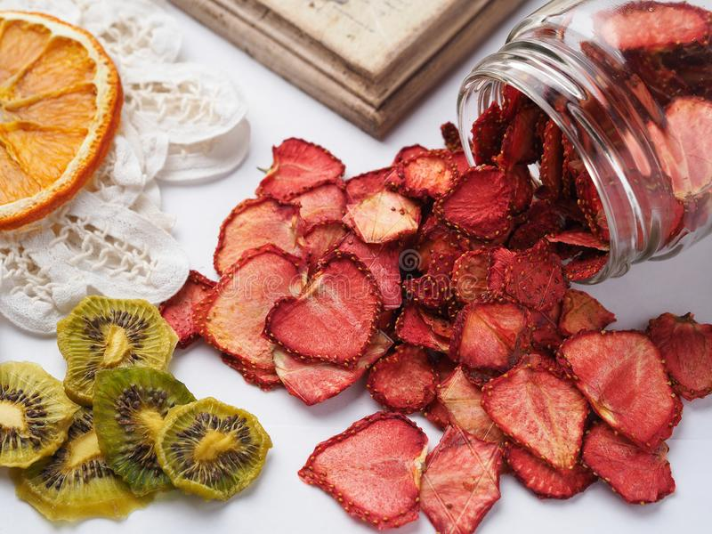 Homemade slices of dried oranges, strawberry and kiwi on white background, top view royalty free stock photos