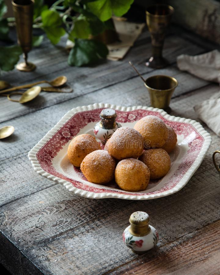 Homemade small round ball donuts sprinkled with powdered sugar on vintage plate. With pink ornament on grey wooden table with vintage powder shakers, towel royalty free stock photos