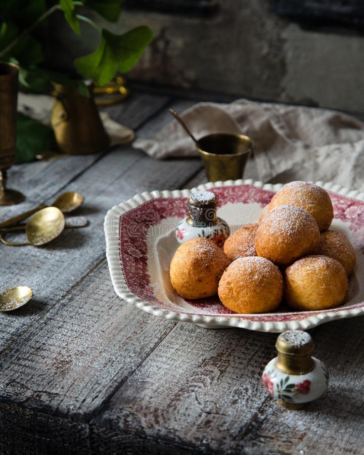 Homemade small round ball donuts sprinkled with powdered sugar on vintage plate. With pink ornament on grey wooden table with vintage powder shakers, towel stock photography