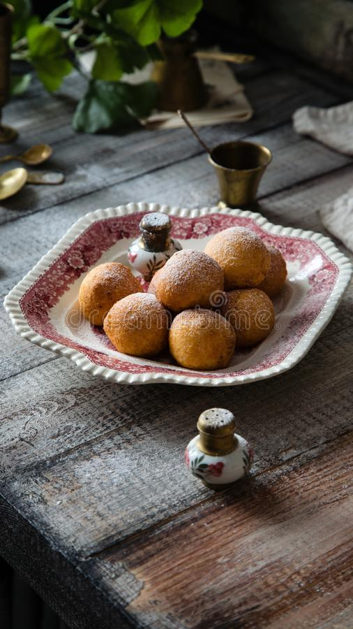 Homemade small round ball donuts sprinkled with powdered sugar on vintage plate. With pink ornament on grey wooden table with vintage powder shakers, towel royalty free stock photo